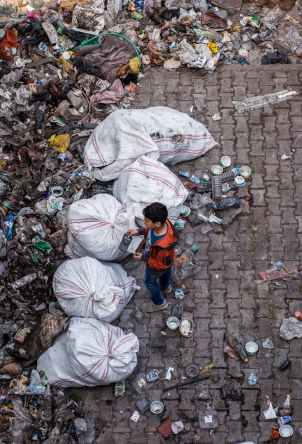 child standing near garbage